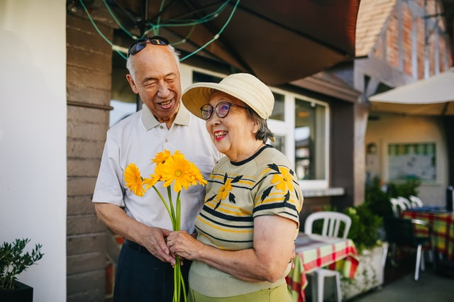 Inclusive Approach to Authentic Buyer Personas: elderly Asian couple holding yellow flowers